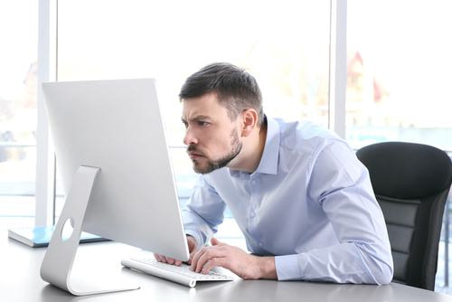 Man hunched over computer